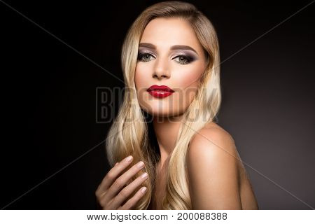 Beautiful blonde model girl with long curly hair . Hairstyle wavy curls . Red lips . Fashion , beauty and make up portrait