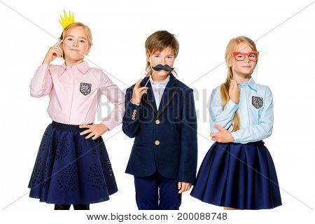 School, educational concept. Three joyful children in school uniform posing at studio with different masks. Isolated over white background. Copy space.