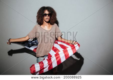 Photo of serious african young lady standing dressed in USA flag. Looking camera.