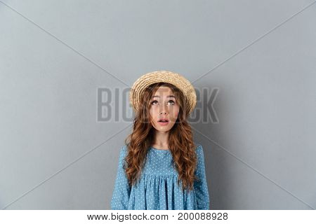 Image of shocked young pretty woman standing over grey wall wearing hat. Looking aside.