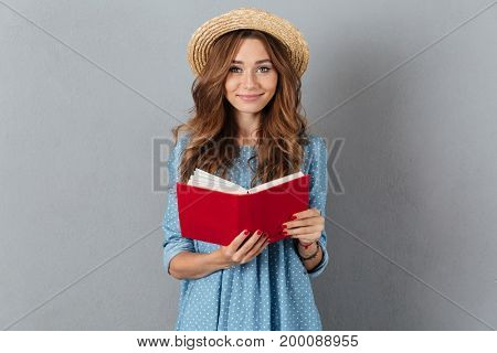 Picture of cheerful young pretty woman standing over grey wall wearing hat reading a book. Looking camera.