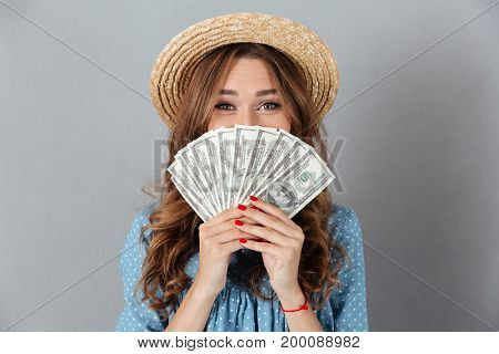 Picture of excited young happy woman standing over grey wall wearing hat covering face with money. Looking camera.