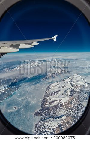 Airplane viewof the Greenland with mountain, ocean and ice holes with part of airplain
