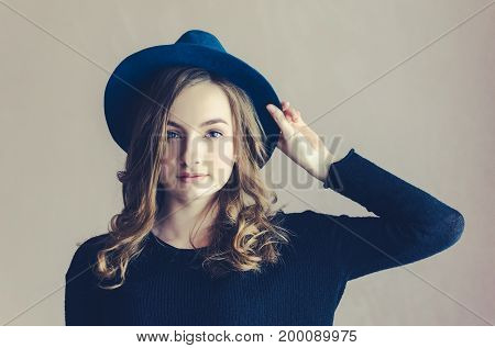 Portrait of beautiful smiling hipster teenage girl with long fair curly hair in a blue hat and black jumper looking at the camera. Lifestyle and people concept. Toned image.