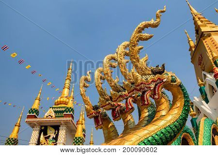 Close up beautiful naga sculpture on with budhist temple and blue sky in background