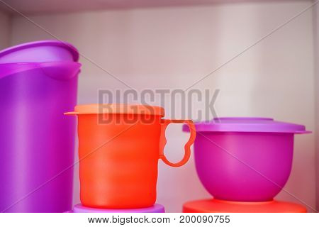 Close up modern plastic container, bowl and jug on shelf in kitchen