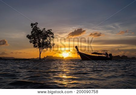 Silhouette of thai long tail boat on the sea at the sunset Khlong Muang beach Krabi Thailand