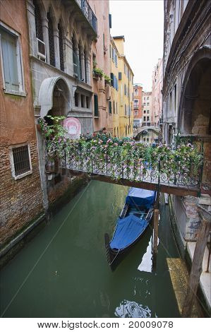 View along Venice canal with floral bridge