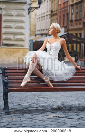 Full length shot of a beautiful ballerina sitting on the bench in the city center looking away thoughtfully.