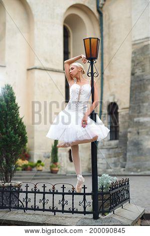 Vertical full length shot of a beautiful ballerina standing near street lamp looking away dreamily beauty urban city grace elegance.