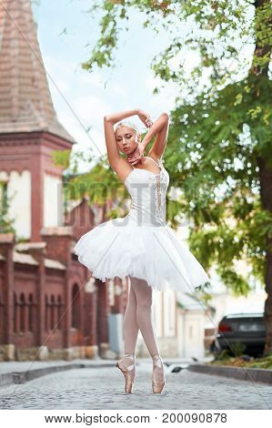 Full length portrait of a beautiful young ballerina dancing sensually on the street of an old beautiful town grace femininity beauty sensuality.