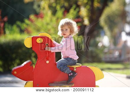 Funny baby on playground in autumn park