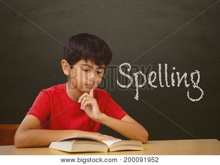 Digital composite of Student boy at table against grey blackboard with spelling text