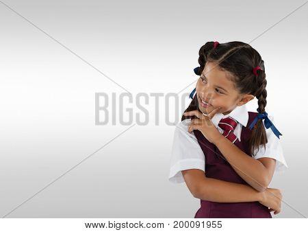Digital composite of Schoolgirl thinking in front of grey background