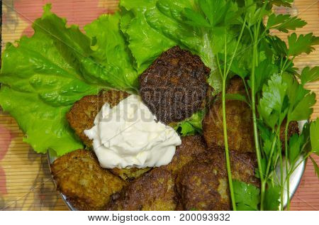 A metal plate with potato pancakes stands on a bamboo mat.