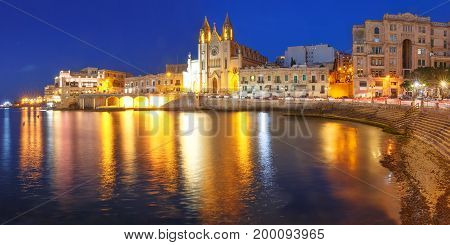 Panorama of Balluta Bay and Neo-Gothic Church of Our Lady of Mount Carmel, Balluta parish church, during evening blue hour, Saint Julien, Malta