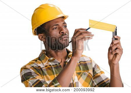 focused african american builder with measuring tool isolated on white