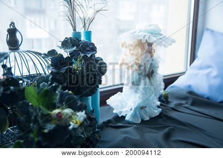 On The Windowsill, Artificial Blue Flowers And A Doll