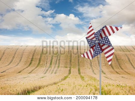 Digital composite of USA wind catchers in front of country crop field and sky