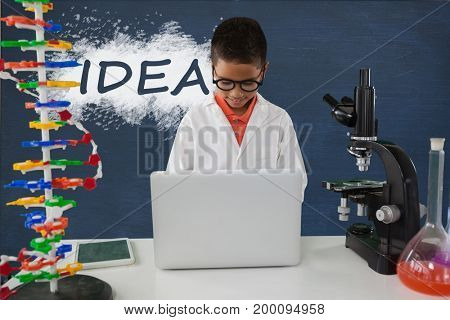 Digital composite of Student boy at table using a computer against blue blackboard with idea text