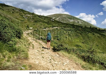A woman is traveling in the mountains