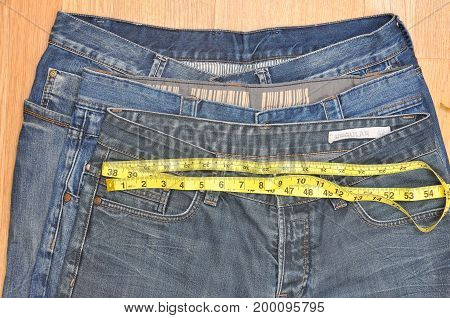 Measuring different size of jeans. Concept of losing weight, smaller size of jeans