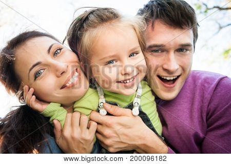 Low angle view portrait of happy smiling family in autumn. Focus on woman