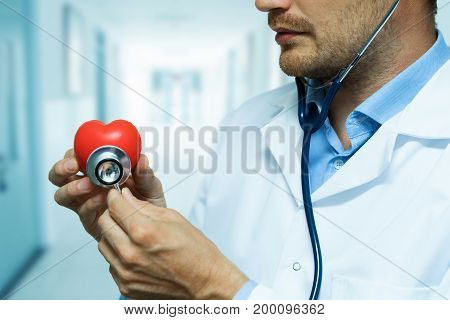 cardiologist checking red heart with stethoscope. cardiology concept