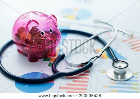 healthcare budget concept - stethoscope and piggy bank on graphic charts
