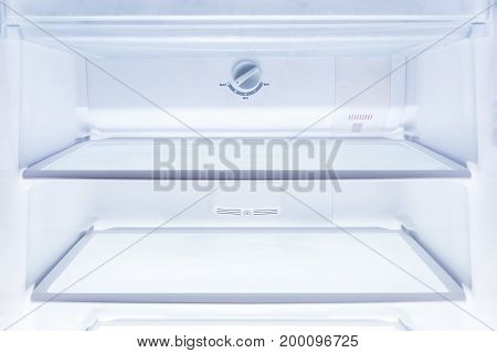 inside of clean and empty refrigerator with shelves good background for health or diet concept