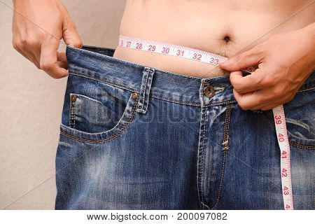 Concept of Man losing weight. Men wearing big jeans after diet.