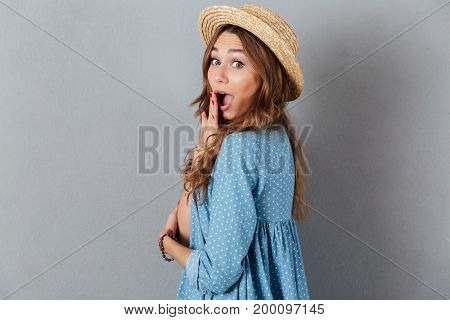 Picture of shocked young pretty woman standing over grey wall wearing hat. Looking camera.