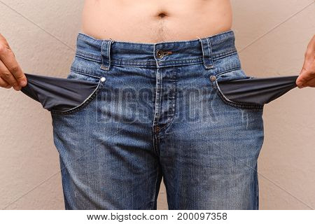 Man showing his empty pockets. Concept of poorness, jeans with empty pockets