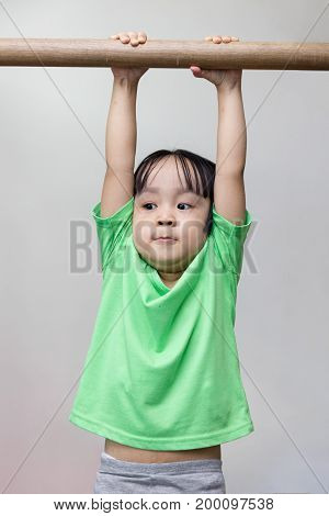 Asian Chinese Little Girl Hanging On Horizontal Bar
