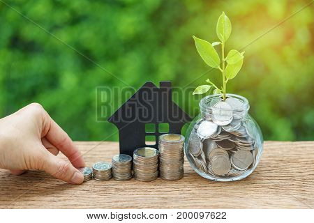 growth sprout plant in jar with full of coins and hand holding stack of coins with paper house as property or mortgage investment concept.