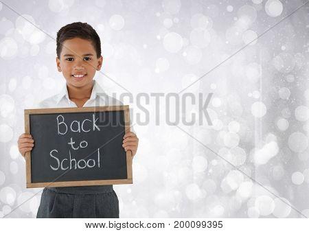 Digital composite of Schoolboy holding back to school blackboard in front of bright bokeh background