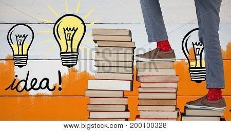 Digital composite of Feet walking up book stairs with colorful light bulb graphics and orange painted wall