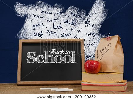 Digital composite of Back to school blackboard on Desk foreground with blackboard graphics of school subjects