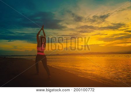 Silhouette young woman practicing yoga on the beach at sunset. Vintage tone
