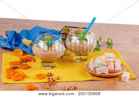 A wooden table with a plate of Turkish delight, two glasses of grated walnuts, dried apricots and green leaves of mint, orange physalis, isolated on a white background.