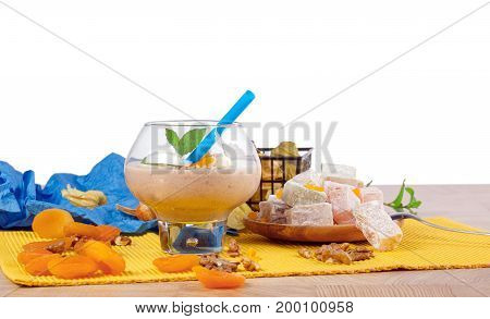 A glass of cocktail, green leaves of mint, orange dried apricots, walnuts, a wooden plate of Turkish delight, rahat lokum or lokum, silver spoon, isolated on a white background.