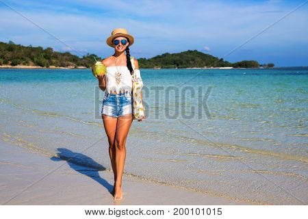 Tanned young happy girl by the sea. Dressed in denim shorts, a white top, a straw hat, sunglasses, a bag of pineapple, coconut drink, white sand, azure water, a holiday on a tropical island, Boho