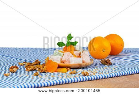 A wooden table with two juicy oranges, a plate of Rahat lokum or Turkish delight, dried apricots and walnuts, fresh green leaves of mint, isolated on a white background. poster