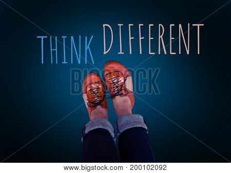 Digital composite of Think Different text and red shoes on feet with blue background