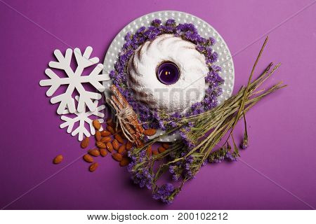Top view of white snowflakes, almond, sticks of cinnamon, a bouquet of little purple flowers, a plate of a round cake sprinkled with powdered sugar, a candle on a bright violet background. Christmas concept.