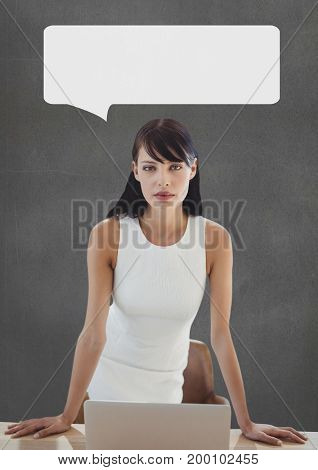 Digital composite of Business woman at table with speech bubble against grey background