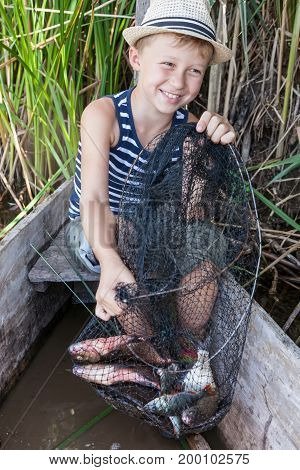 Young fisherman holds a cage with a fish caught by bream and a perch