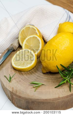 Slices half fresh juicy lemon with rosemary and knife on the vintage wooden table.