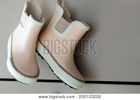 Pink little children rubber boots concept of autumn or spring background.