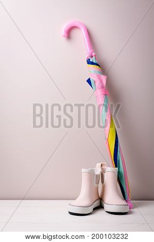 Pink little children rubber boots with colorful umbrella concept of autumn or spring background.